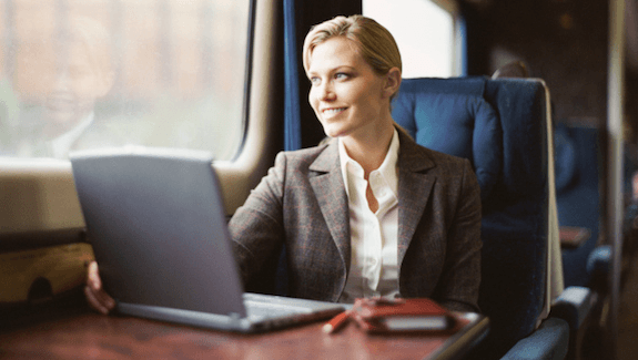 Woman smiling ngelixa esenza Train Business Travel