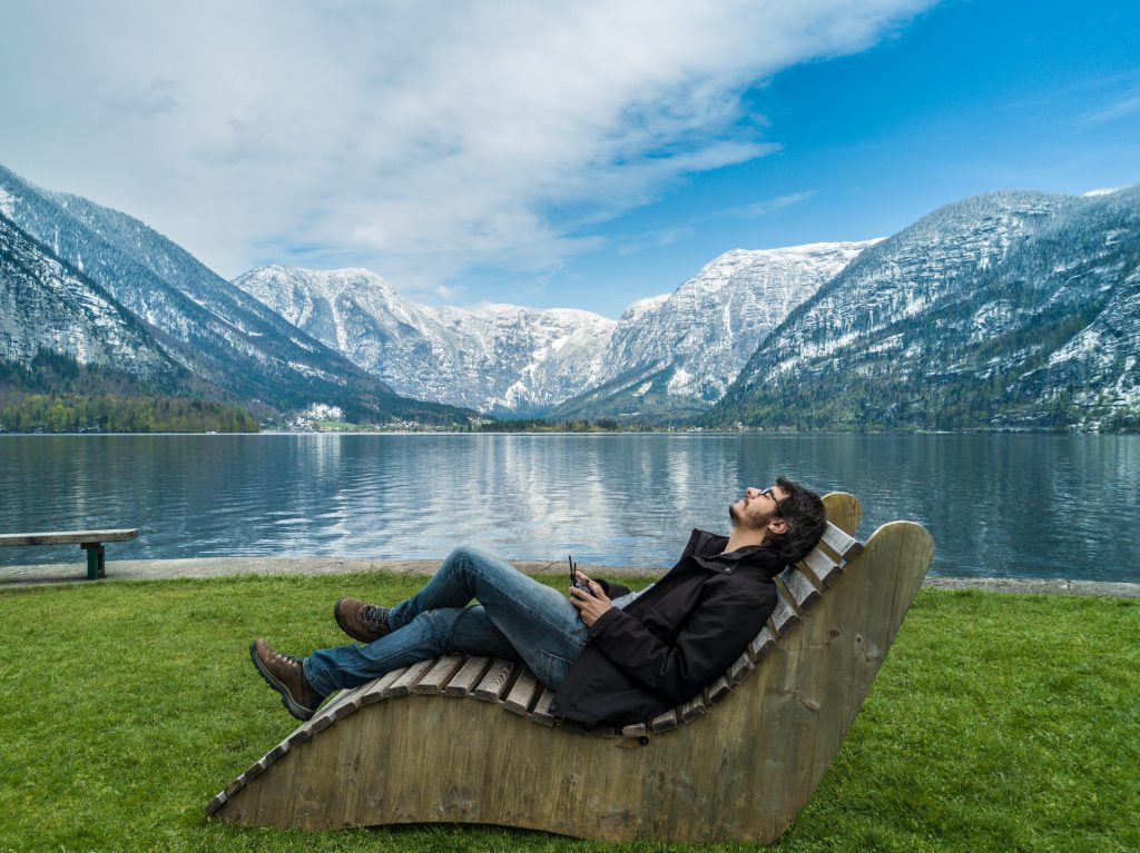 Man sitting next to Hallstatt, Austria lake