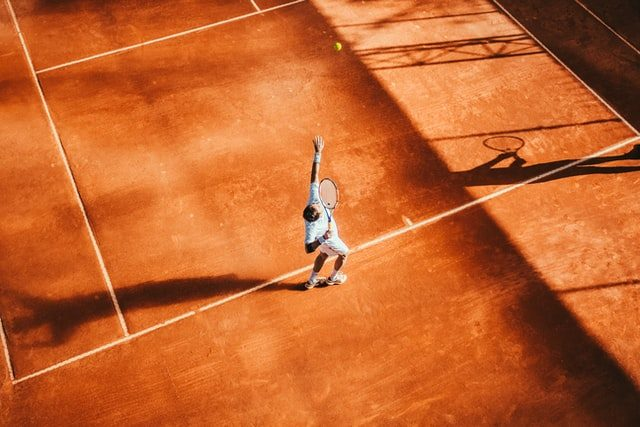 man serving on a clay tennis court in Mouratoglou Tennis Academy